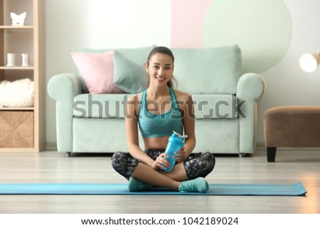 Beautiful sporty woman with bottle of water after doing fitness exercises at home