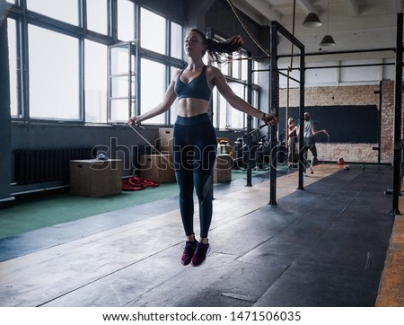 beautiful sporty woman workout with jumping rope in crossfit gym