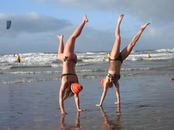 Beautiful sporty young girls with bikini having fun and do handstand on the beach. Waves and kitesurfers on the background.Traditional Dutch new years dive, swimmers with orange ice cab.