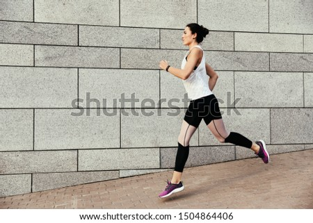 Beautiful sporty young woman running on street, space for text