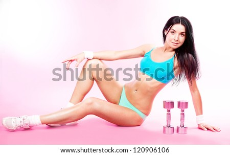 beautiful sporty young woman with dumbbells, against pink studio background