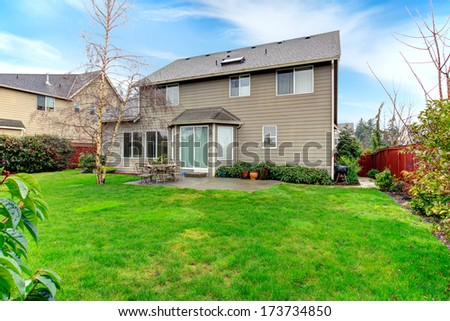 Beautiful spring backyard. Patio with dining table set overlooking green trim and tree