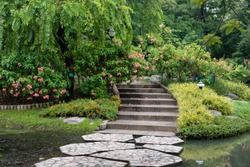Beautiful spring flower with rock walkway in garden at park near lake.Green tree landscape scene photo.Tranquil place.