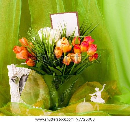 Beautiful spring flowers in a glass vase and ballet-dancer on green background