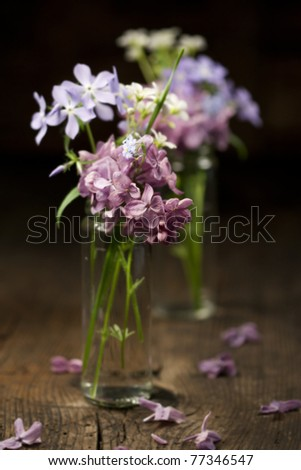 Beautiful spring flowers in a vase on wooden background