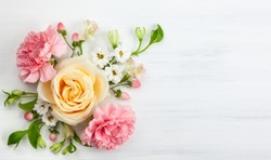 Beautiful spring flowers on white wooden background. Festive floral concept with clean space for text. Top view.