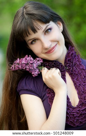 Beautiful spring girl in lilac flowers