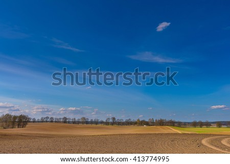 Beautiful spring landscape with plowed field under blue sky with clouds, Polish field. #413774995
