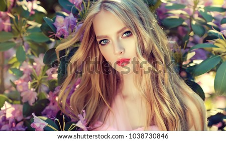 Beautiful spring   model girl   in fragrant   flowers  in summer blossom park. Woman in a blooming garden . Fashion, Cosmetics & Perfumes . Curly blonde hair