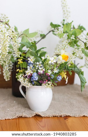Beautiful spring wildflowers on rustic wooden table. Spring rural still life. Blooming colorful flowers of ajuga, forget-me-nots, daffodils, pulmonaria, rabelera holostea, bird cherry Stok fotoğraf ©
