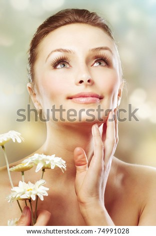 Beautiful Spring Woman with Chamomile flowers. Healthy skin. Skincare