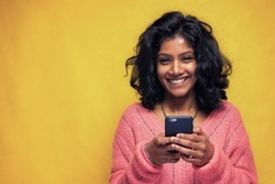 Beautiful Sri Lanka girl makes technology poses with yellow bright background - Young woman uses mobile phone to chatting and messaging