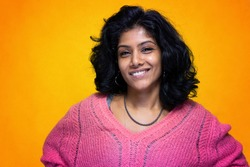 Beautiful Sri Lanka girl poses standing with yellow bright background- Young woman smiles