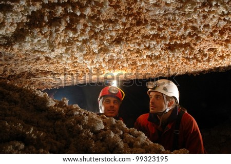 Beautiful stalactites in a cave with two speleologist explorers