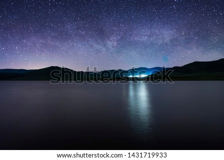 Beautiful starry night. Milky way galaxy over the lake and mountains. Night landscape.