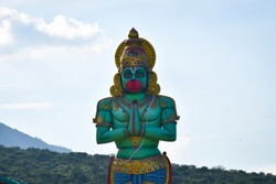 BEAUTIFUL STATUE OF LORD HINDU GOD HANUMAN IN STANDING POSITION WITH MOUNTAIN HILL BACKGROUND WHOSE DEVOTEE OF LORD RAMA IN TAMILNADU COIMBATORE ANUVAVI TEMPLE