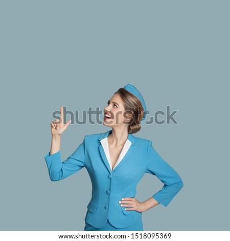 Beautiful stewardess points a finger on copyspace. Blue background.