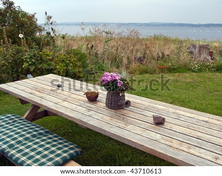Beautiful still life basket of flowers on a wooden picnic table outdoors