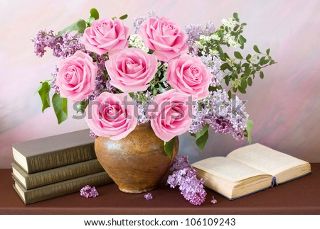 Beautiful still life with lilac and pink roses flowers bouquet, books pile and open book on painting background