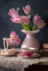 Beautiful still life with tulips, a books, and a cup of tea. still life with flowers, home decor.