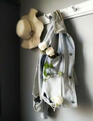 Beautiful stilllife hanging jacket and hat with white flower.