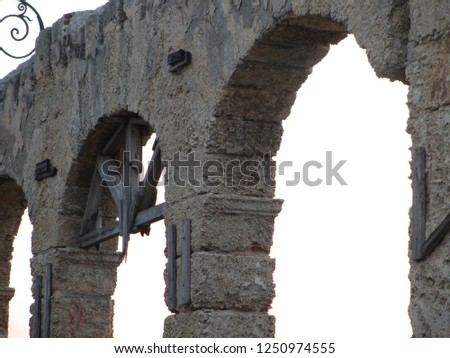 Beautiful stone arches found at a ruin in Old Havana in Cuba. Remnants of an old wooden structure with rusty nails are left in a window frame. Deterioration due to climate and pollution is visible. #1250974555