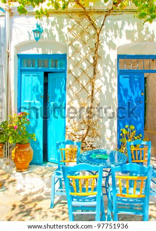 Beautiful stone made road with old traditional houses and traditional iron made blue coffee tables and chairs in Chora the capital of Amorgos island in Greece