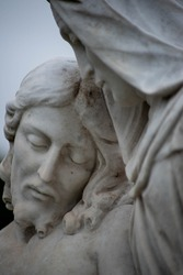 Beautiful stone pieta in a Victorian cemetery. Full frame image in natural light. Selective focus on face of Jesus.