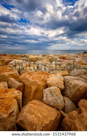 Beautiful stone shore seascape with colorful stones.  Vertical view