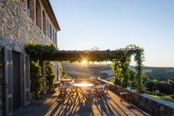 Beautiful stone Tuscan villa at sunrise with sunburst