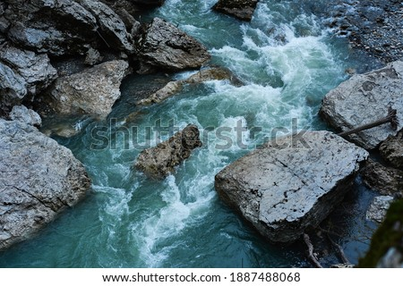 Beautiful stormy mountain river of emerald and blue hues runs over rocks top view. Wild and beautiful nature of Caucasian reserve, river Belaya, Republic of Adygea, Russia.