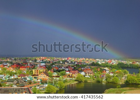 Beautiful stormy weather landscape - rustic houses, lake and foliage against the background of dark blue sky and the bright rainbow on it soon after the rain, Moscow region village, Russia #417435562