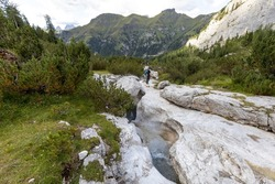 beautiful stream in the eroded rock on Marmolada group. Alps, Dolomites, Passo Fedaia, Trento, Italy