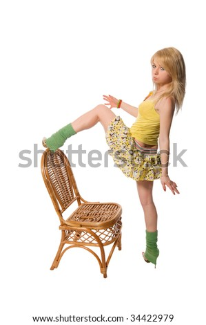 Beautiful stripper wearing yellow dress dancing with the chair isolated on white background