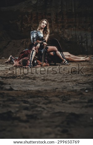 Beautiful strong girl gladiator with sword sitting on a mountain of dead enemies. Ancient Rome