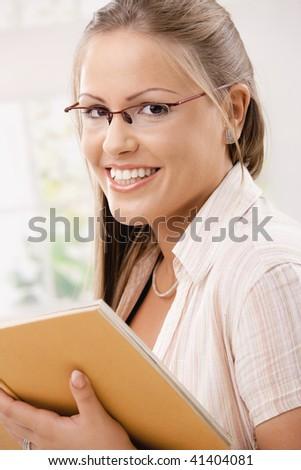 Beautiful student girl reading book, smiling.