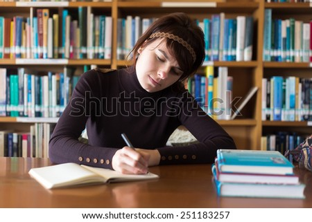 Beautiful student girl studying in college library. Writing notes at her notebook. Selective focus on face.