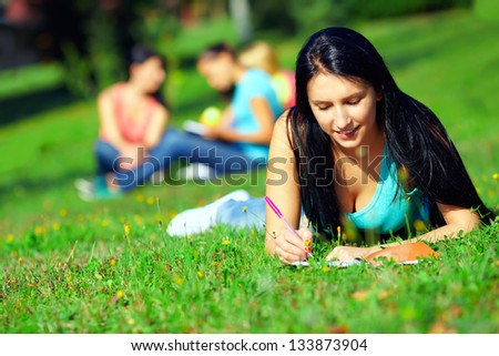 beautiful student on colorful sunny lawn