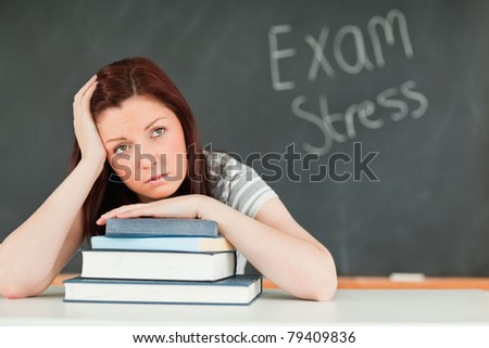 Beautiful student stressed by her examinations in a classroom