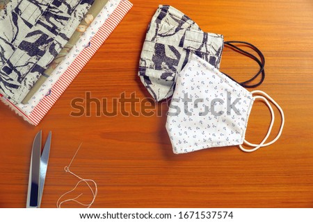 Beautiful 2 style of DIY cotton face mask, scissor and needle on wood table. Protect dust, pollution (PM2.5), Virus, Bacteria, Covid-19. Handicraft, Handmade concept. Copy space for any text design.