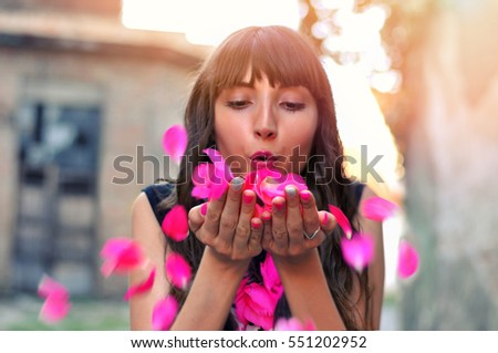 Beautiful styled girl with flowers blowing petals from her hands.Sunlight.Outdoor.Happy Valentines day, love concept