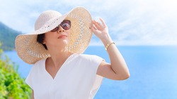 Beautiful & Stylish Asian woman wearing straw beach hat and 100% UV protection sunglasses to protect her eyes and face from sun exposure. Skin aging, Optical, Ultraviolet keratitis, Beauty products.