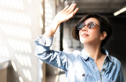 Beautiful / Stylish Asian woman wearing 100% UV light eyes protection sunglasses, stand and raise her hand to block out bright glare and sunlight from outside to avoid ultraviolet rays over exposure.