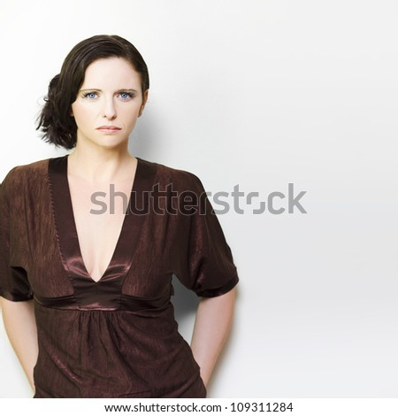 Beautiful stylish brunette woman with an unsmiling unimpressed expression staring directly at the camera isolated on white in an Unhappy woman concept