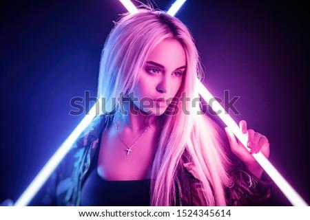 beautiful stylish fashionable girl in bodysuit posing in photo Studio on dark background in neon light #1524345614