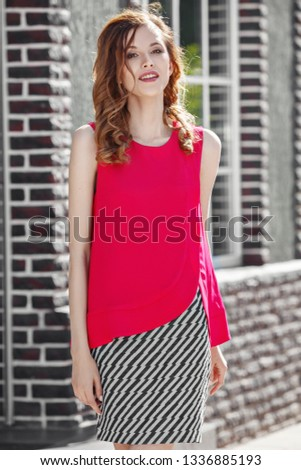 927eb662c2 Beautiful stylish girl dressed in fuchsia color top and black and white  skirt poses in the