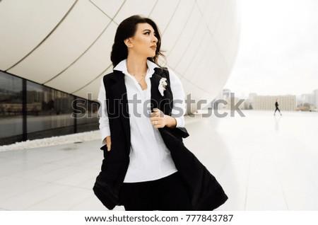 beautiful stylish girl in black fashion suit walks on a background of modern buildings in Baku