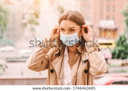 Beautiful stylish girl wear medical face mask on sunny city street. Young elegant happy hipster woman put on protective face mask outdoors. Urban fashion outfit, lifestyle. COVID-19 quarantine, travel