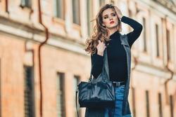 Beautiful stylish girl with handbag posing near old building .