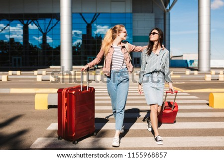 Beautiful stylish girls in sunglasses happily walking along pedestrian strip with red suitcases and airport on background